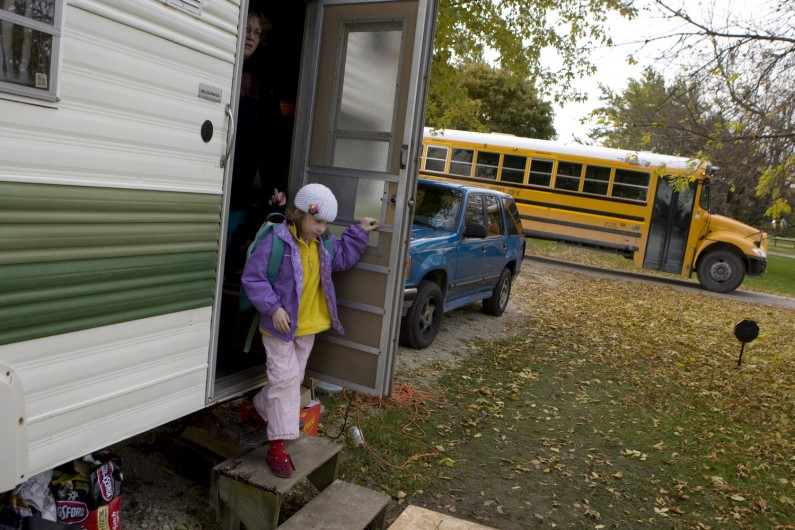 A school bus pulls up in front of the camper  to pick up Mariah for school.