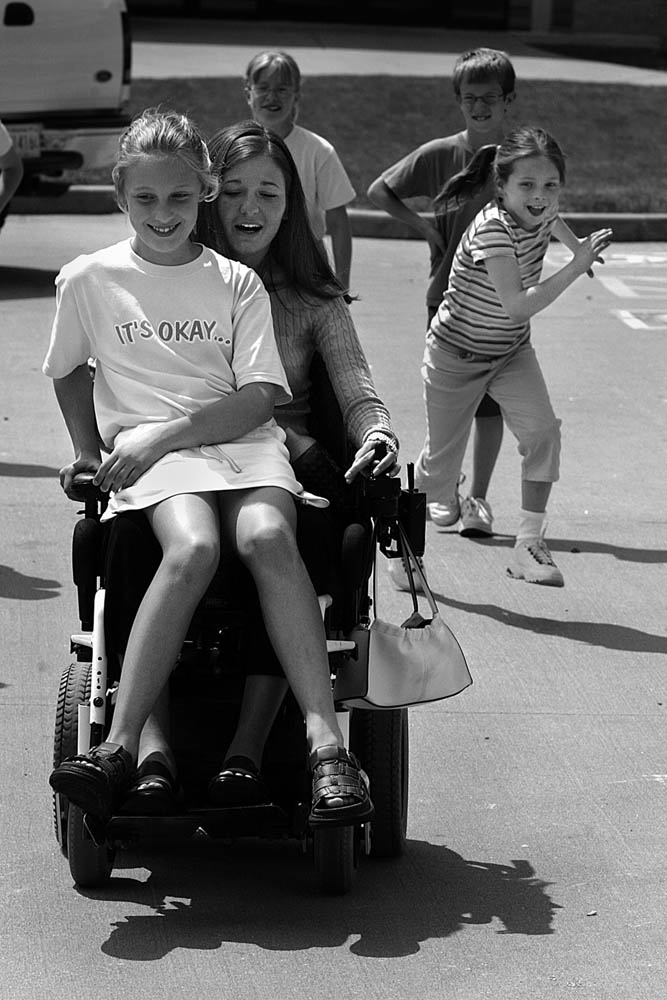 At Precious Blood School, student teacher Kelly often drew a crowd at recess who pleaded for wheelchair rides. Elizabeth Theil was the lucky rider on this day.