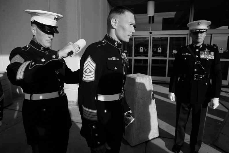 No part of the Marine dress blue uniforms goes uninspected and at the airport before the arrival of Lueken's body, Staff Sgt. Kevin Bruce, center, used a lint roller on the back of 1st Sgt. Troy Euclide.