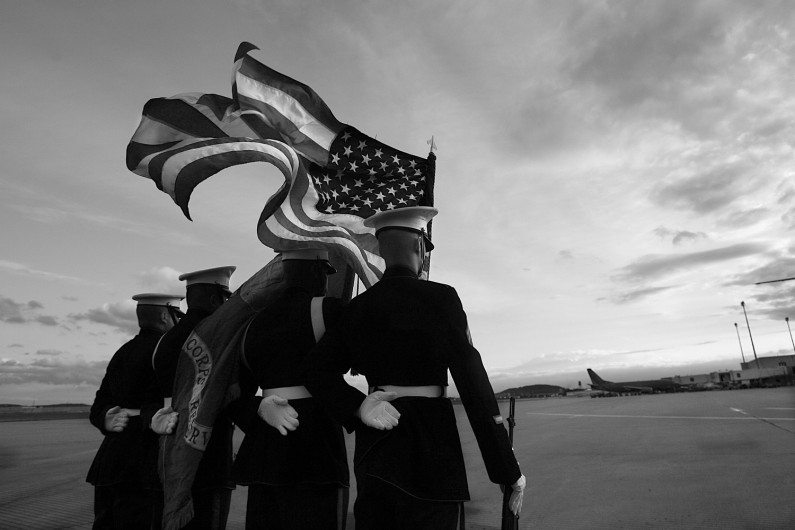 Summary: Marines do not abandon each other, which is why the corps escorts its fallen brothers all the way to their final resting places. That mission falls to the Marine Casualty Assistance Team – Marines who emphasize precision in ceremony and support for the family.  Caption:A Marine color guard stood at parade rest at sunset on May 11 as it and fellow Marines awaited the return of a fallen brother, Cpl. Eric Lueken, of Dubois, who was killed April 22  while serving in Iraq.