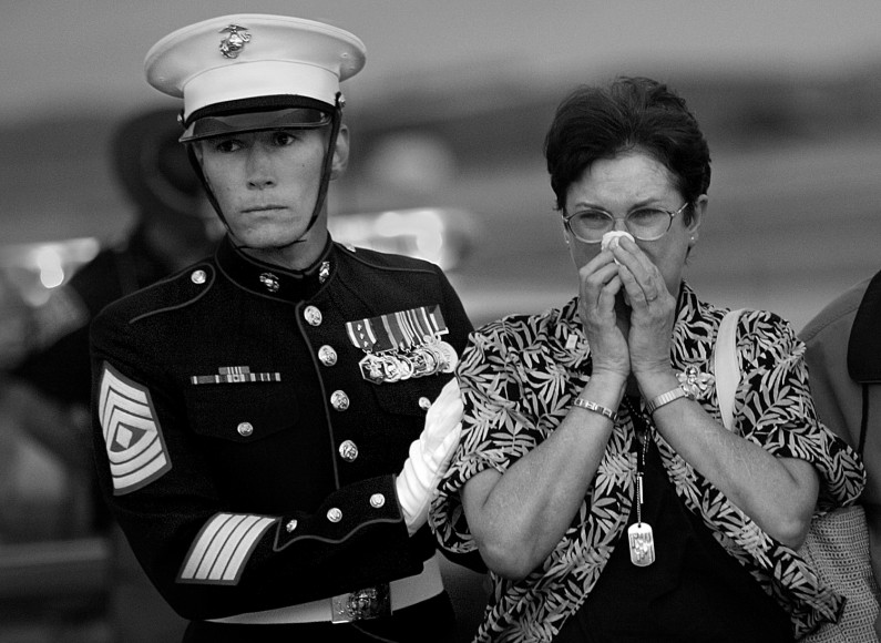As Marine pall bearers began to remove the casket from the plane's cargo hold, 1st Sgt. Troy Euclide gathered in Melinda Lueken as the Marines marched closer and closer. Euclide stood close to Melinda since word of her son's death and has been constant source of comfort.