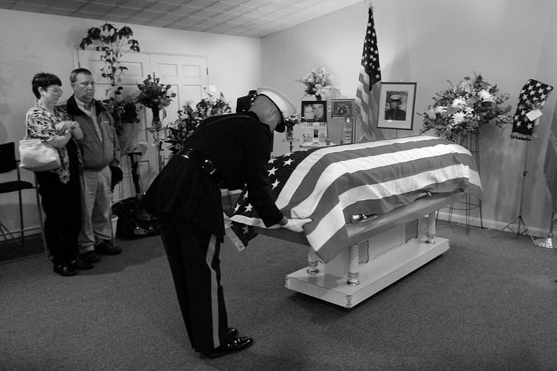 "Melinda and Glenn ""Jake"" Lueken, of Dubois, watched as Maj. Randall Hoffman untucked the flag on the casket of their son, Eric."