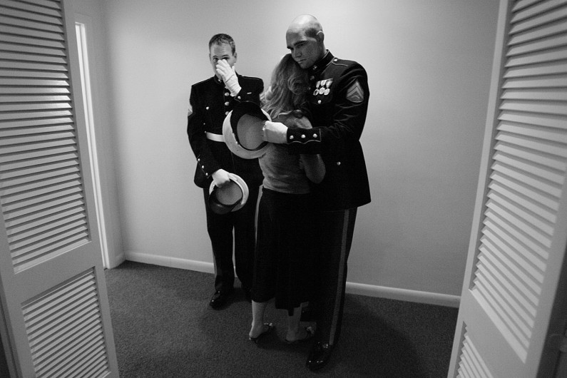 Lueken's cousin, Holly Vonderheide, of Jasper, hugged Cpl. Ryan Schmitt as he and Cpl. Jeremy Schnarr,  wiped away tears in a back hallway following a purple heart ceremony at the funeral home.