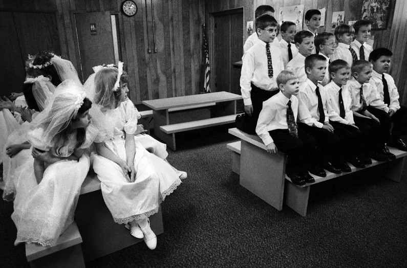 Before being placed in a mandatory boy-girl arrangement, the 10 girls and 13 boys about to make their first communion at St. Raphael's Church in Dubois arranged themselves in the church basement for the beginning of Mass.