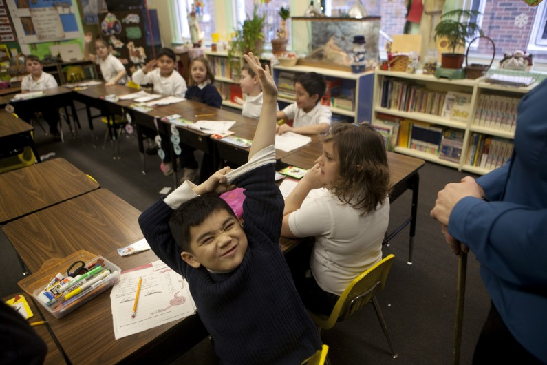 Second-grader Kevin Nguyen gives his raised hand extra support as he tries to express to teacher Julie Dillenburg that he knows the answer to a word question at St. Patrick Grade School in Joliet. St. Pat's, as it is affectionately known, is the oldest Catholic school in the Joliet diocese.