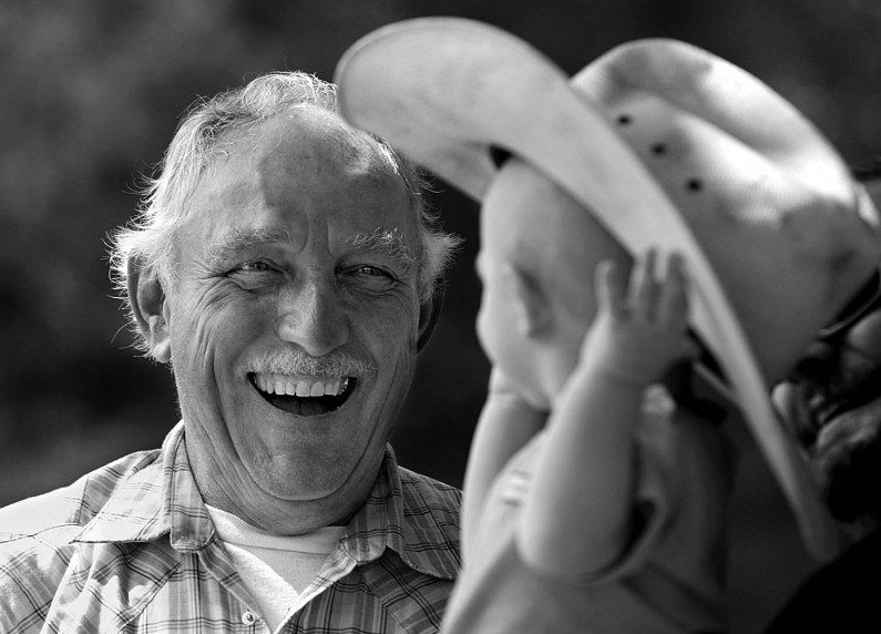 Doc Ellis, left, a member of the Holland town council, laughed as he watched the head of Owen Hunefeld, 1, disappear under Ellis' hat as they stood under a shade tree at the Holland Community Festival in Holland Park. Ellis was talking to Chad and Jamie Hunefeld, of Holland, when Owen, in the arms of his father, reached for Ellis' hat.