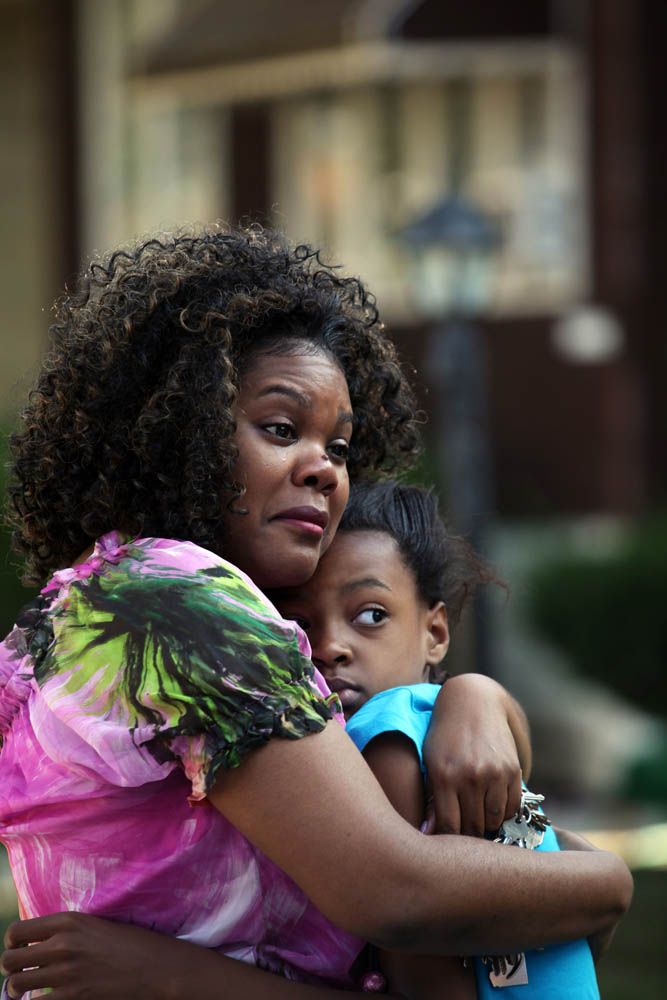 Dunn Elementary School Principal Chandra Byrd-Wright hugs Tanesha Swain, 10, outside her Chicago home, where Tanesha's sister, Taccara Swain, 15, was shot in the head. Taccara was caught in the crossfire of a gunfight, according to police reports.