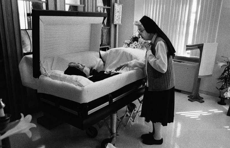Sister Mary Edward Heckel, 96, says good-bye and gives a blessing to Sister Veronica Marie Knies. Sister Veronica Marie died on Good Friday and the sisters she lived with at the infirmary held a special wake in the chapel.